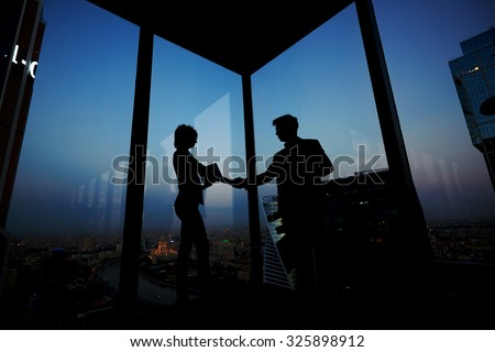 Silhouette of businessman shaking hands in honor of the transaction with his new woman partner, male and female entrepreneurs congratulate each other with their successful work - stock photo