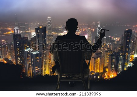 Silhouette of businessman sit on chair and hold a cigar, looking the harbor of Victoria at Hong Kong, Asia. - stock photo