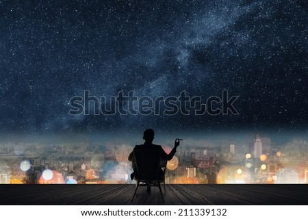 Silhouette of businessman sit on chair and hold a cigar unger the stars. - stock photo