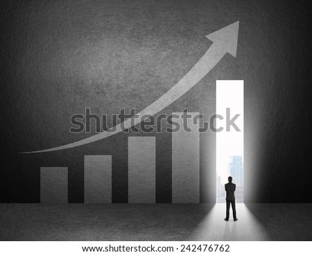Silhouette of businessman stand in front of the growth chart on the wall. - stock photo