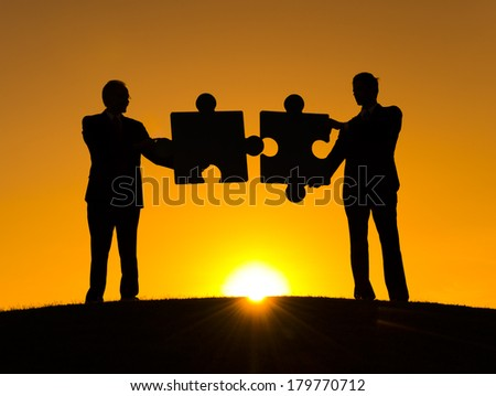Silhouette of Businessmen Connecting Jigsaw Puzzle at Sunset