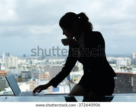 Silhouette of businesswoman work near window in hotel room. - stock photo