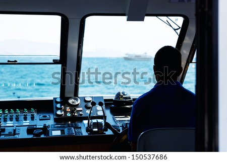 Silhouette of captain steering boat - stock photo