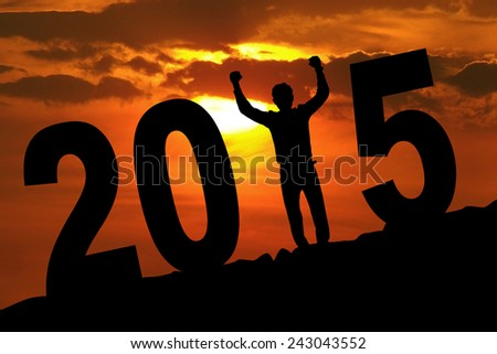 Silhouette of cheerful man forming number 2015 at the hill on sunset time - stock photo