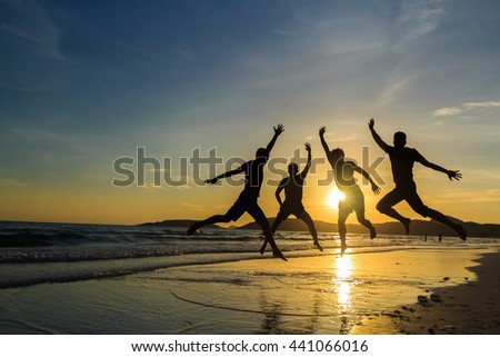 Silhouette of cheering young generation jumping on sunrise beach,Business concept idea - stock photo