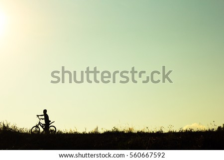 Silhouette of children cyclist riding Movement on the background of a beautiful sunset.