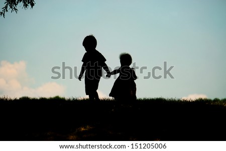 Silhouette of children holding hands - stock photo