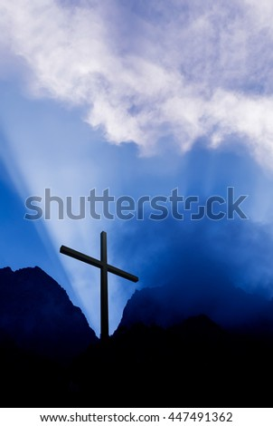 Silhouette of Christian cross at sunrise or sunset vertical image - stock photo