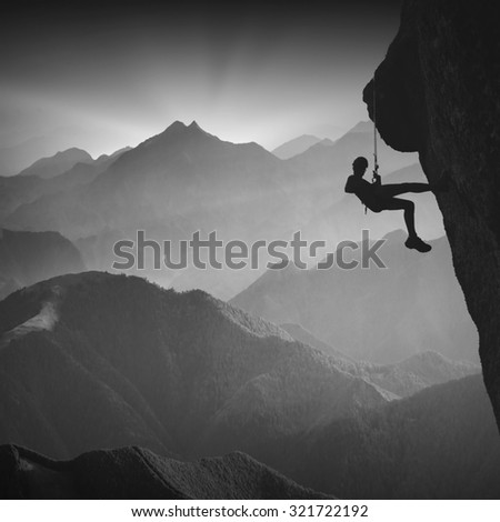 Silhouette of climber on a cliff against misty mountain valley. Black and white - stock photo