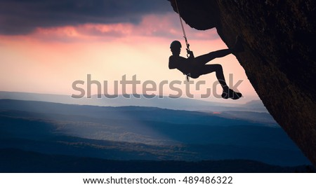 Silhouette of climber on a cliff against misty mountain valley in a sunset light. Extreme sport.