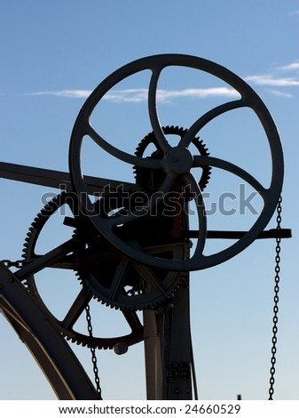 Silhouette of cogs, wheels and chains against a blue sky