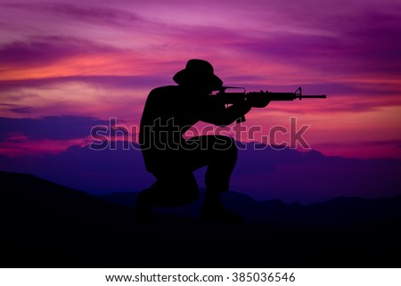 Silhouette of combat soldier with US styled weapons. (Artist drawn silhouette on photo background)