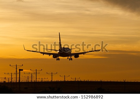 Silhouette of commercial jet landing at LAX during a dramatic sunset.