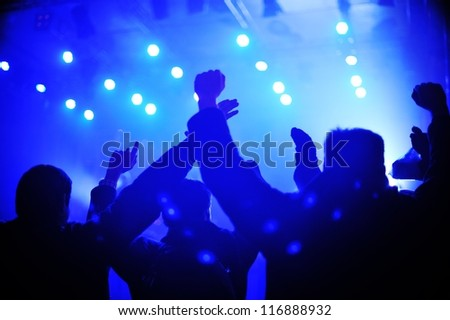 Silhouette of concert crowd in front of stage lights - stock photo