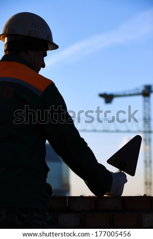 silhouette of construction mason worker bricklayer installing red brick with trowel putty knife outdoors - stock photo
