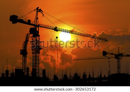 silhouette of construction site crane in sunset