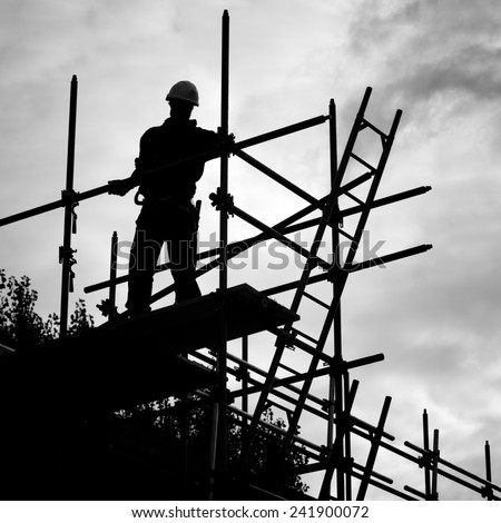 silhouette of construction worker against sky on scaffolding with ladder on building site.Monochrome - stock photo
