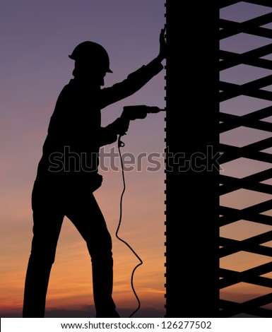 Silhouette of construction worker against sunset sky - stock photo