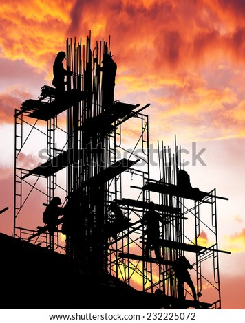 silhouette of construction worker on scaffold  - stock photo