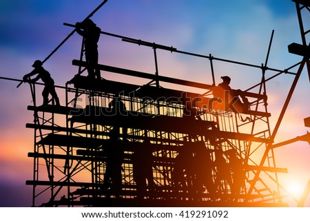 Silhouette of construction workers working on high availability and security. - stock photo