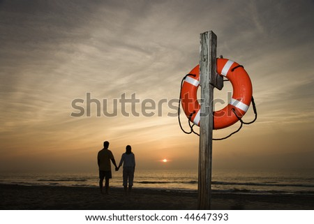 Silhouette of couple holding hands on beach watching the sunset with life preserver in foreground - stock photo