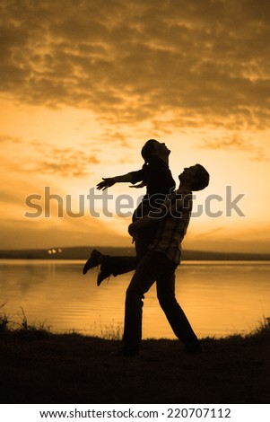 silhouette of couple man and woman jumping up holding hands and body against sunset sky with clouds Summer background Symbol of victory success active and achieving - stock photo