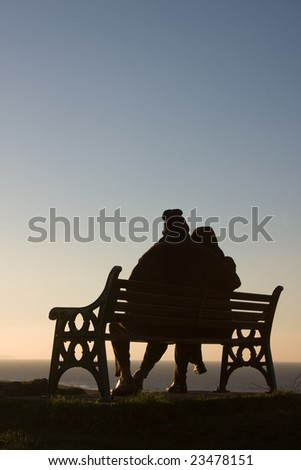 Silhouette of couple on bench - stock photo