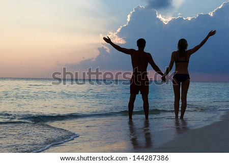 Silhouette Of Couple Walking Along Beach At Sunset