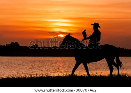 silhouette of Cowboy sitting on his horse at river sunset background - stock photo