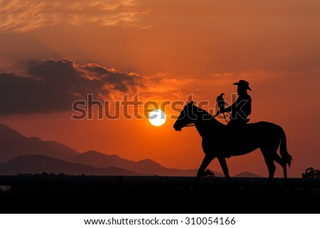 silhouette of Cowboy sitting on his horse at  sunset background - stock photo