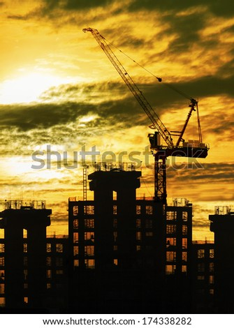 silhouette of crane and building construction and sun set sky with copy space use for construction industry business theme - stock photo