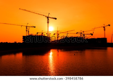Silhouette of crane and building under construction against a sunset sky. - stock photo