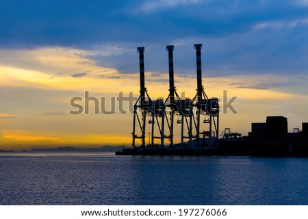 Silhouette of crane at port with blue sky background. - stock photo