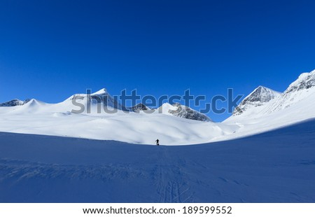 Silhouette of cross country skier with sled on the horizon in Arctic Sweden. - stock photo