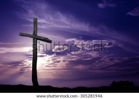 Silhouette of cross over purple sunrise or sunset  - stock photo