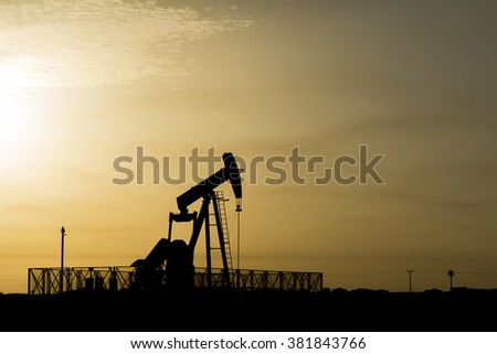 Silhouette of crude oil pump at sunset in oil field.