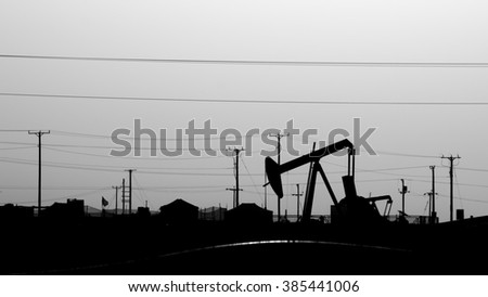 Silhouette of crude oil pump at  sunset in oil field - Black and white