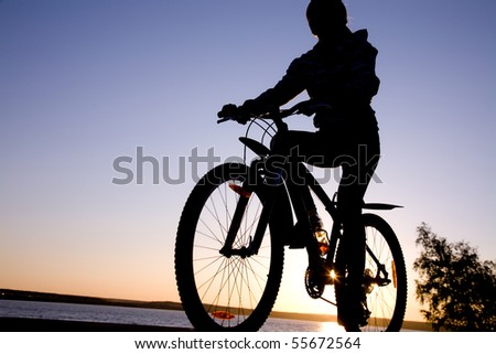 silhouette of cyclist in motion on the background of beautiful sunset - stock photo