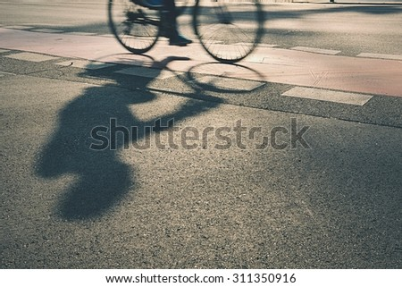 Silhouette of cyclist on the street at sunrise - stock photo