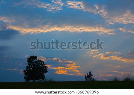 Silhouette of Cyclists mother with child and tree during sunset - stock photo