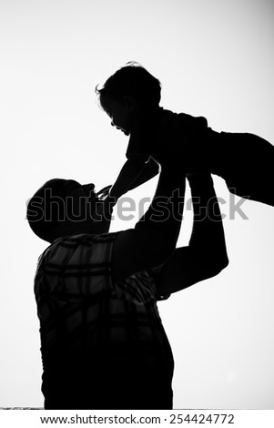 Silhouette of dad holding young son up against blue sky - stock photo