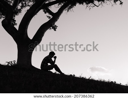 Silhouette of depressed man sitting under the tree. - stock photo