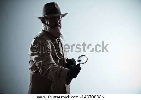 Silhouette of detective with mustache and hat. Holding magnifying glass. Studio shot. - stock photo