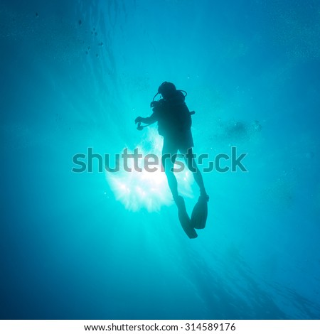 Silhouette of diver with sun disk behind - stock photo
