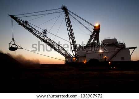 silhouette of drag line working on mine at sunrise with beautiful skies - stock photo