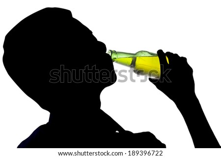 Silhouette of drunk man drinking a bottle of beer - stock photo
