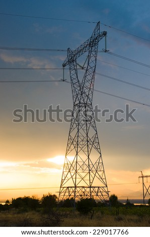 silhouette of electricity pylon and cables at the sunset  - stock photo