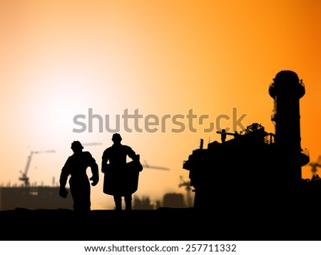 Silhouette of engineer looking at blueprints in a building site over Blurred Power Plant - stock photo
