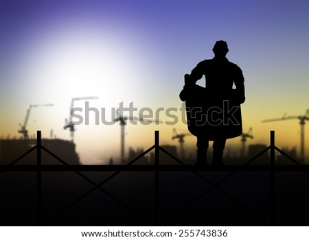 silhouette of engineer looking at blueprints on scaffold in a building site over Blurred construction site - stock photo