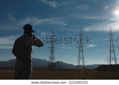 silhouette of engineer standing on field with electricity towers, talking on the phone - stock photo